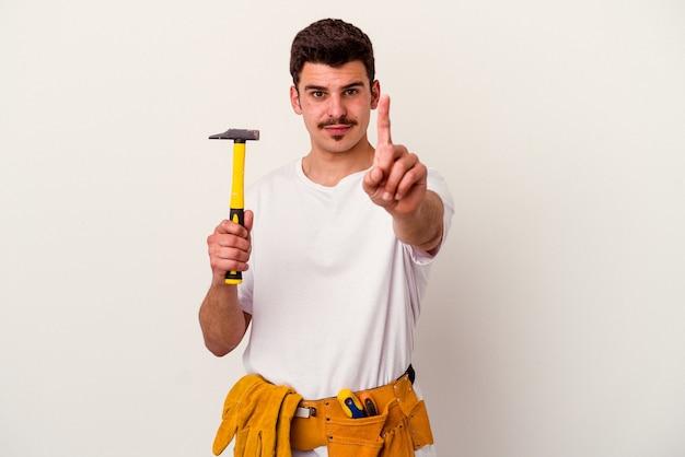 Junger kaukasischer arbeitermann mit werkzeugen lokalisiert auf weißem hintergrund, der nummer eins mit dem finger zeigt.