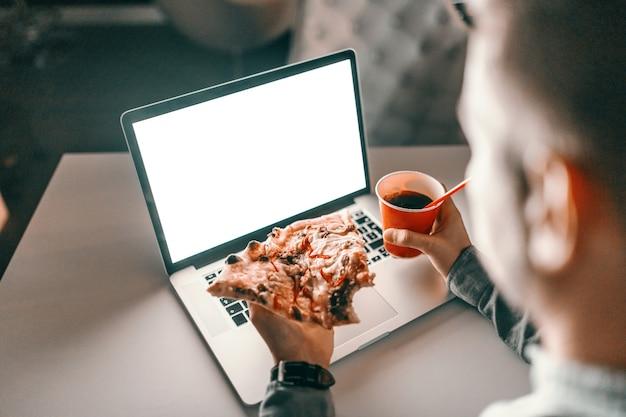 Junger kaukasischer architekt, der pizza isst und saft im büro trinkt.