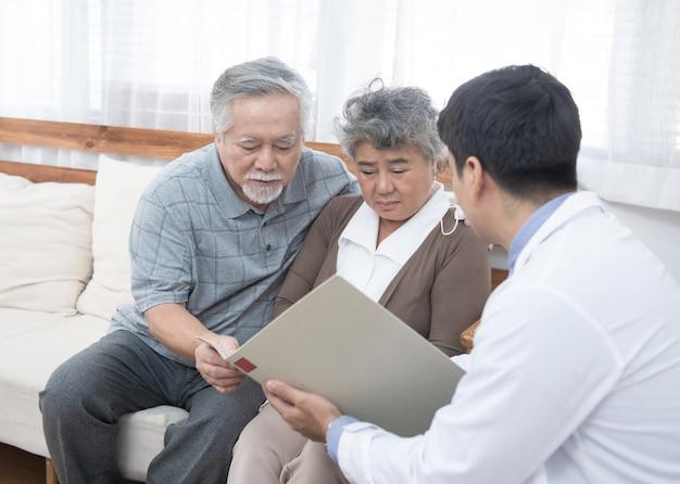 Junger kaukasischer arztmann, der ergebnis der untersuchung auf tablette zu älterer älterer alter asiatischer ruhestandfrau mit altem mann spricht, kümmert sich um sie neben. gesundheitsfürsorge und medizinisches konzept.