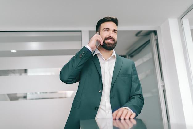 Junger kaukasischer bärtiger geschäftsmann, der im flur steht und smartphone für geschäftsanruf verwendet.