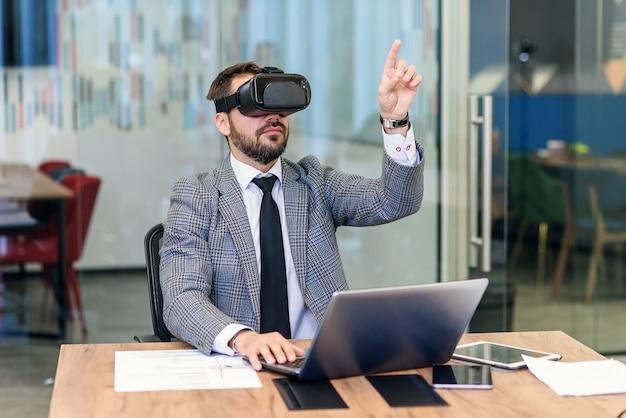 Junger kaukasischer bärtiger geschäftsmann im blauen anzug unter verwendung der vr-schutzbrille im büro.