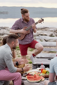 Junger kaukasischer bärtiger mann, der die gitarre spielt, während mit freunden außerhalb der stadt nahe see am schönen sommerabend rumhängt