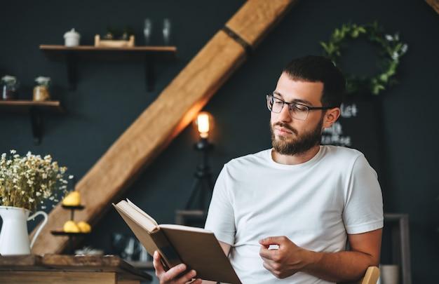 Junger kaukasischer bärtiger mann, der ein buch in der küche liest. freizeit zu hause.