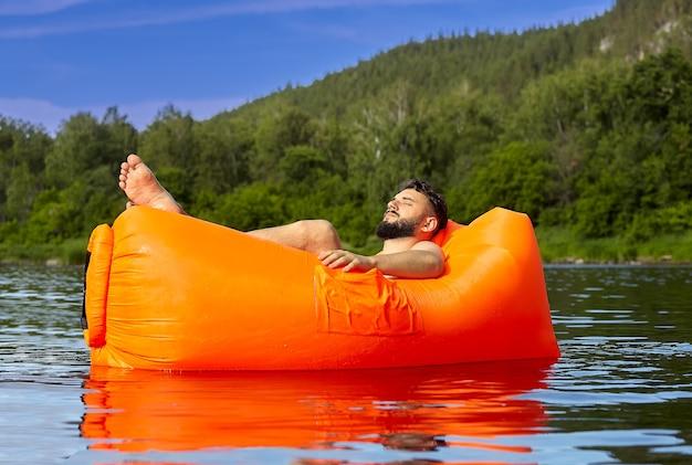 Junger kaukasischer bärtiger mann entspannt sich auf orangefarbenem luftsofa, das auf fluss neben wald, ökotourismus schwimmt.