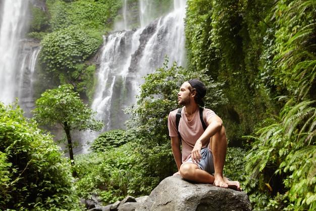 Junger kaukasischer barfüßiger männlicher tourist mit rucksack, der auf felsen sitzt, der durch regenwald umgeben ist und herrliche ansicht mit wasserfall bewundert