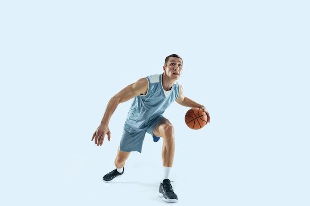 Junger kaukasischer basketballspieler gegen weißen studiohintergrund