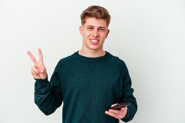 Junger kaukasischer blonder mann, der ein telefon lokalisiert auf weißem hintergrund freudig und sorglos zeigt, das ein friedenssymbol mit den fingern zeigt.