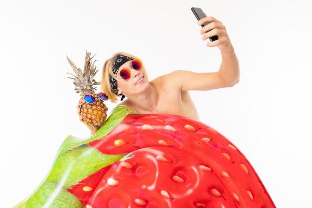 Junger kaukasischer blonder mann steht im badeanzug mit großer gummi-strandmatratze machen selfie mit ananas isoliert auf weißer wand