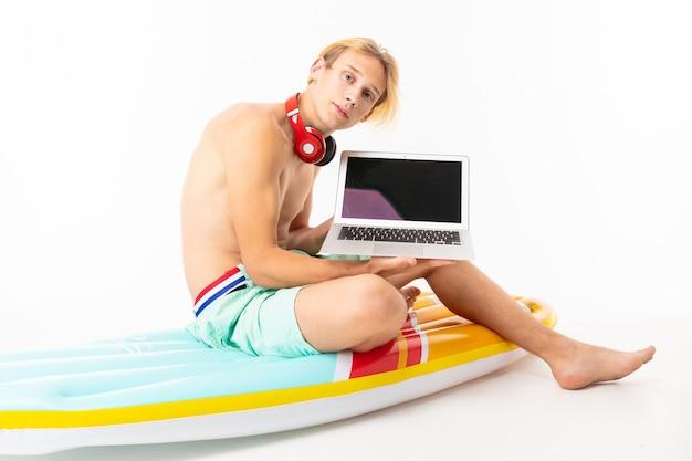 Junger kaukasischer blonder mann steht im badeanzug sitzt auf großer gummi-erdbeer-matratze und arbeitet mit laptop isoliert auf weißer wand