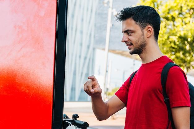 Junger kaukasischer büroangestellter, der ein fahrrad auf einem roten touchscreen mietet