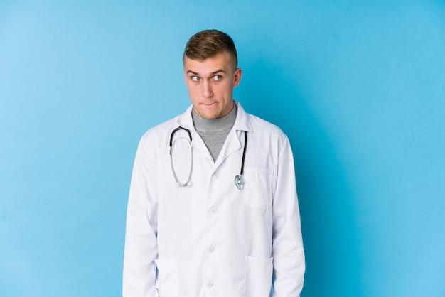 Junger kaukasischer doktormann verwirrt, fühlt sich zweifelhaft und unsicher.