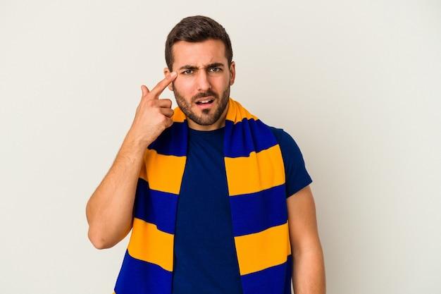 Junger kaukasischer fan einer fußballmannschaft lokalisiert auf weißer wand, die eine enttäuschungsgeste mit zeigefinger zeigt.
