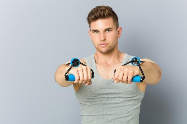 Junger kaukasischer fitnessmann, der mit einem gummiband übt.