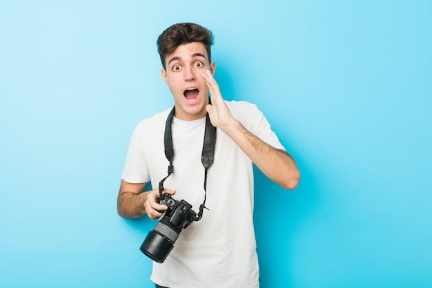 Junger kaukasischer fotograf mann, der eine kamera hält, die aufgeregt nach vorne schreit.
