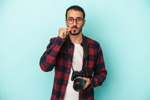 Junger kaukasischer fotograf mann isoliert auf blauem hintergrund mit den fingern auf den lippen, die ein geheimnis halten.