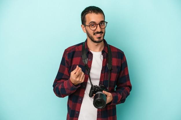 Junger kaukasischer fotografenmann einzeln auf blauem hintergrund, der mit dem finger auf sie zeigt, als ob er einladen würde, näher zu kommen.