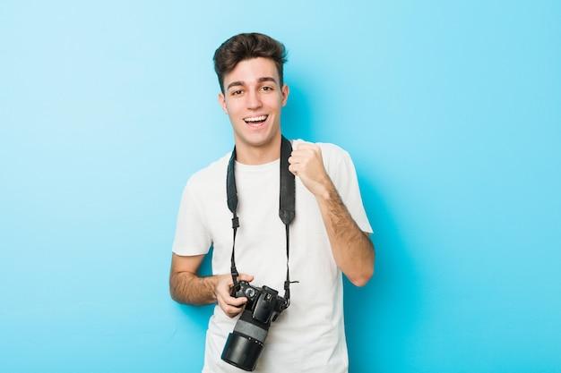 Junger kaukasischer fotografmann, der ein kamerazujubeln sorglos und aufgeregt hält