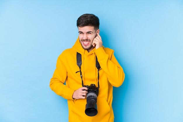 Junger kaukasischer fotografmann, der ohr mit hand bedeckt.