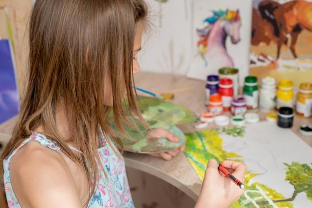 Junger kaukasischer frauenmaler, der im segeltuch im kunststudio arbeitet