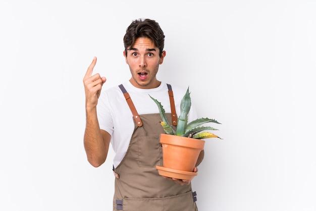 Junger kaukasischer gärtnermann, der eine anlage lokalisiert hält, eine idee, inspirationskonzept habend.