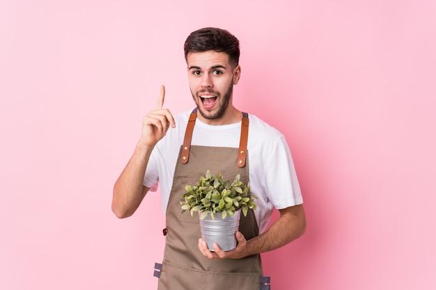 Junger kaukasischer gärtnermann, der eine pflanze hält, die eine idee hat