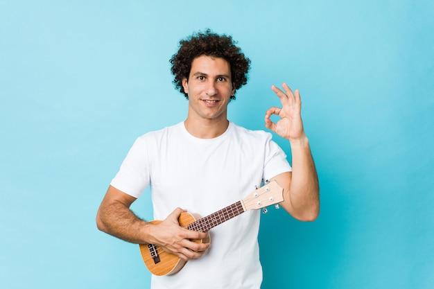Junger kaukasischer gelockter mann, der das ukelele nett und überzeugt spielt, okaygeste zeigend.