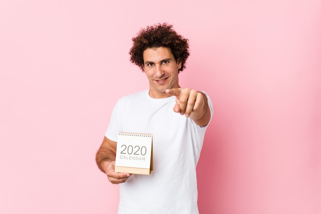 Junger kaukasischer gelockter mann, der ein freundliches lächeln des kalenders 2020 zeigt auf front hält.
