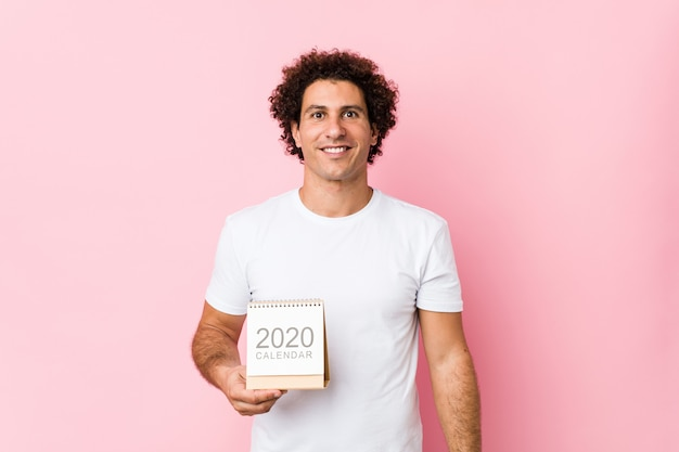Junger kaukasischer gelockter mann, der einen kalender 2020 glücklich, lächelnd und nett hält.