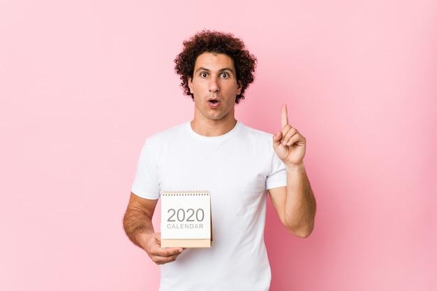 Junger kaukasischer gelockter mann, der einen kalender 2020 hat irgendeine großartige idee, konzept der kreativität hält.