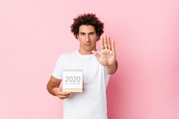 Junger kaukasischer gelockter mann, der einen kalender 2020 steht mit der ausgestreckten hand zeigt das stoppschild und verhindert sie hält.