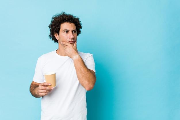 Junger kaukasischer gelockter mann, der einen mitnehmerkaffee seitlich schaut mit zweifelhaftem und skeptischem ausdruck hält.
