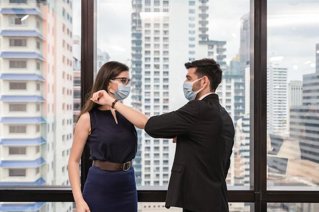 Junger kaukasischer geschäftskollege, der gesichtsmaske und ellbogenstoßgruß im büro trägt