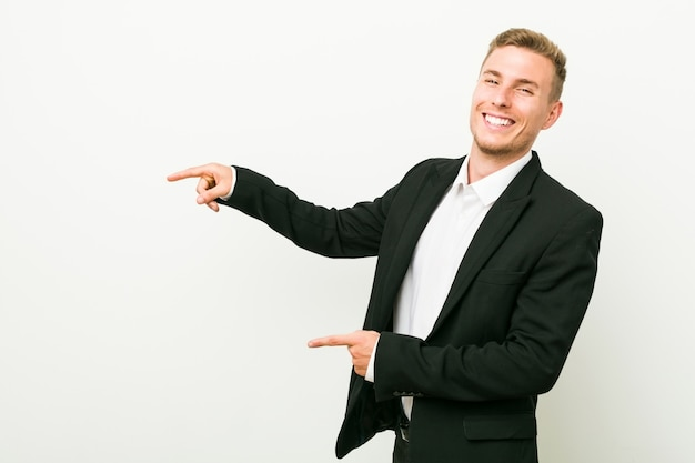 Junger kaukasischer geschäftsmann aufgeregt, zeigend mit den zeigefingern weg.