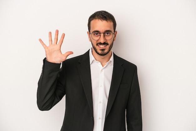 Junger kaukasischer geschäftsmann, der auf weißem hintergrund lokalisiert wird, lächelt fröhlich und zeigt nummer fünf mit den fingern.