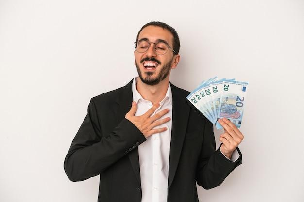 Junger kaukasischer geschäftsmann, der banknoten auf weißem hintergrund hält, lacht laut und hält die hand auf der brust.