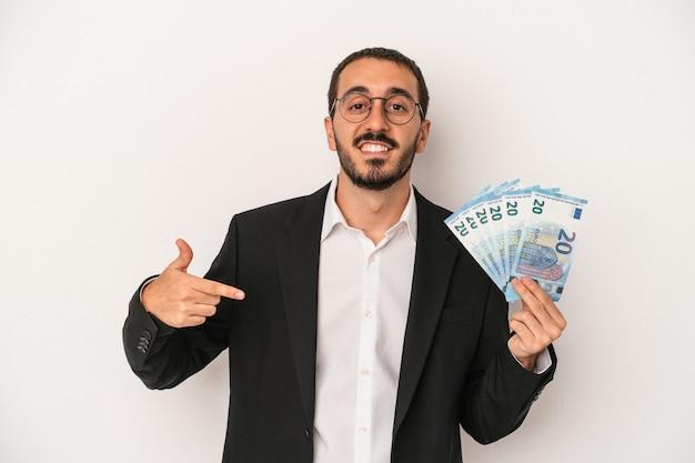 Junger kaukasischer geschäftsmann, der banknoten einzeln auf weißem hintergrund hält, der mit der hand auf einen hemdkopierraum zeigt, stolz und selbstbewusst