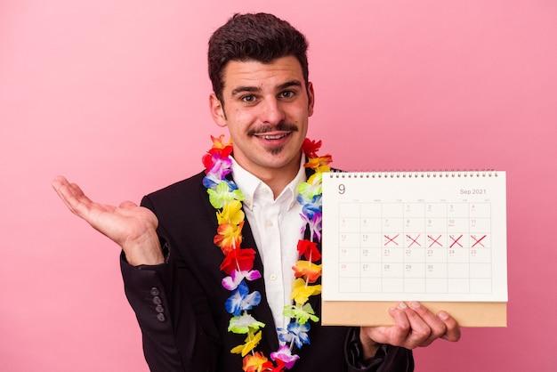 Junger kaukasischer geschäftsmann, der die tage für den urlaub zählt, einzeln auf rosafarbenem hintergrund, der einen kopienraum auf einer handfläche zeigt und eine andere hand an der taille hält.