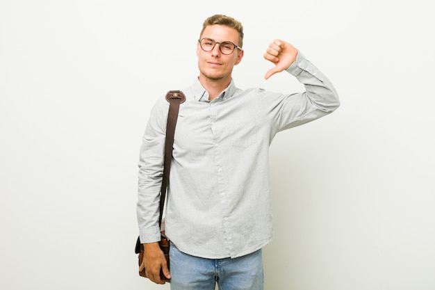 Junger kaukasischer geschäftsmann, der eine abneigungsgeste zeigt, daumen nach unten