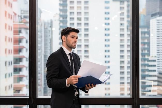 Junger kaukasischer geschäftsmann, der finanzdokument hält und im büro schaut