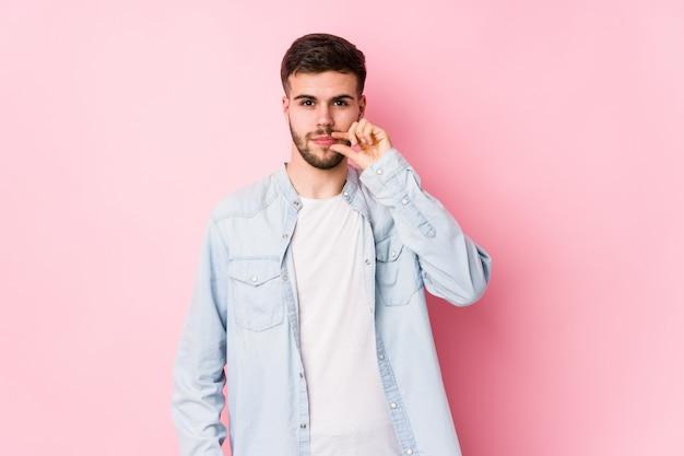 Junger kaukasischer geschäftsmann, der in einer weißen wand posiert, die mit den fingern auf den lippen lokalisiert wird, die ein geheimnis halten