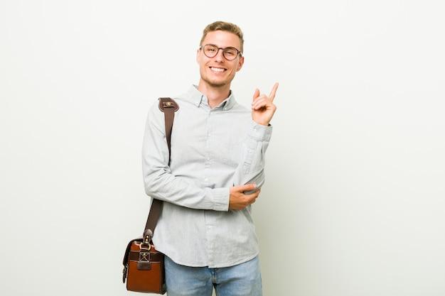 Junger kaukasischer geschäftsmann, der mit dem zeigefinger weg freundlich zeigen lächelt