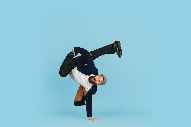 Junger kaukasischer geschäftsmann, der spaß beim tanzen des breakdance auf blauem studiohintergrund hat
