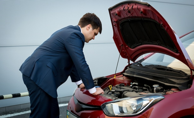 Junger kaukasischer geschäftsmann, der versucht, einen abgestürzten automotor zu reparieren?