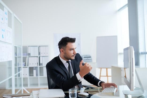 Junger kaukasischer geschäftsmann in der klage, die im büro sitzt und bildschirm betrachtet