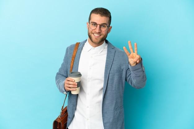 Junger kaukasischer geschäftsmann lokalisiert auf blauem hintergrund glücklich und zählt drei mit den fingern