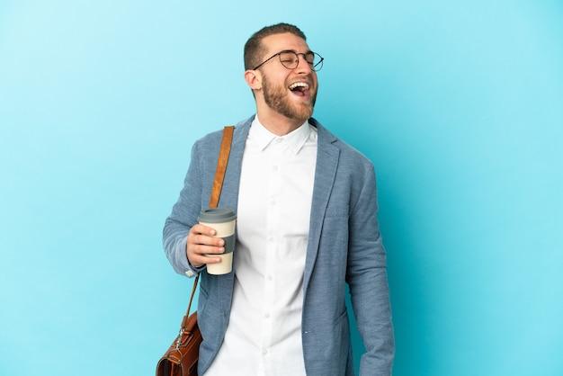 Junger kaukasischer geschäftsmann lokalisiert auf blauem hintergrund lachend