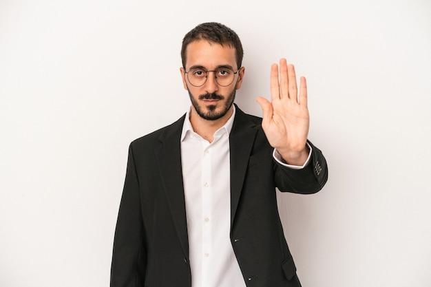 Junger kaukasischer geschäftsmann lokalisiert auf weißem hintergrund, der mit ausgestreckter hand steht und stoppschild zeigt und sie verhindert.