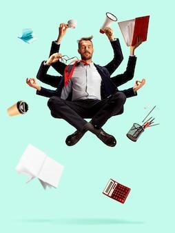 Junger kaukasischer geschäftsmann, manager, der alles verwaltet, viele dinge. frist, zeitmanagement. moderner shiva, ruhig und ausgewogen. büroarbeit, tägliche aufgabe. papiere, kaffee, ordner, bleistifte.