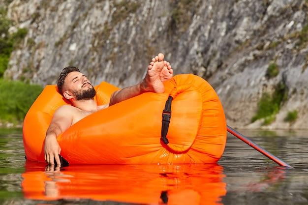 Junger kaukasischer geschäftsmann mit bart schläft auf der orangefarbenen aufblasbaren liege im wasser, die auf dem fluss neben dem berg geht, es gibt handy in der hand, ökotourismus.