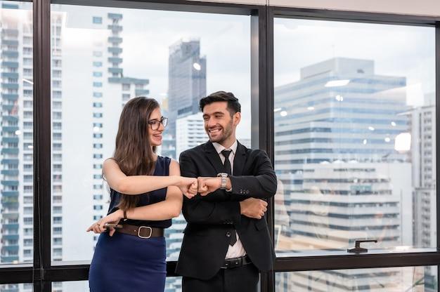 Junger kaukasischer geschäftspartner, der fauststoß und glück im büro gibt